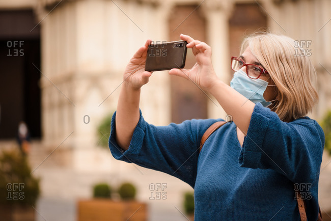 Adult female traveler in eyeglasses and medical mask for coronavirus prevention taking pictures of medieval architecture while standing against blurred exterior of old building in Cuenca town in Spain