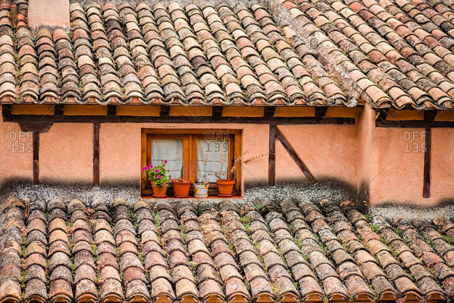 Exterior of aged stone building with weathered terracotta tiles on roof and potted flowers near small window on street of Cuenca town in Spain