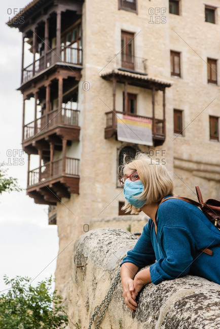 Low angle side view of travelling woman in protective mask leaning on stone border near old building and looking away while visiting medieval town Cuenca in Spain