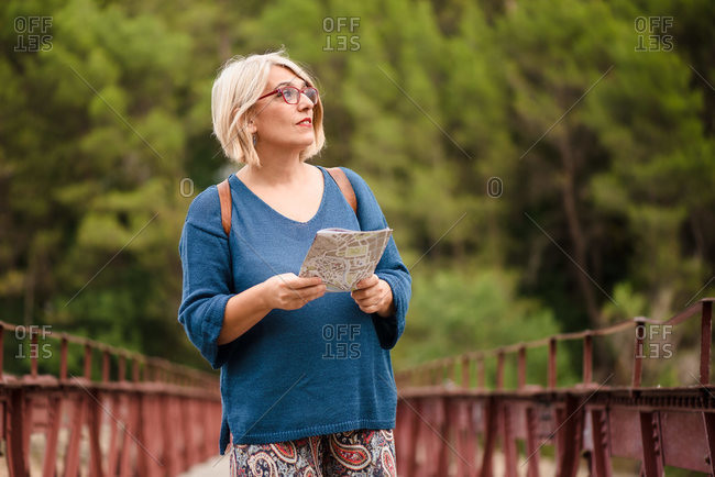 Adult female tourist holding map and looking away while standing on footbridge against green forest and searching for direction during travel in Spain