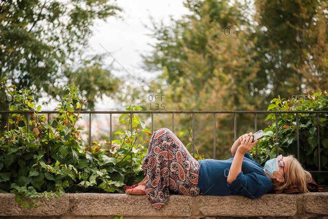 Full body side view of female traveler in protective mask lying on stone border against green trees and browsing mobile phone while relaxing during sightseeing in Cuenca town in Spain