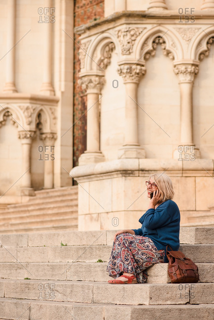 Side view of female tourist in protective mask sitting on stairs near column of medieval stone building and talking on smartphone while resting during sightseeing in Cuenca town in Spain