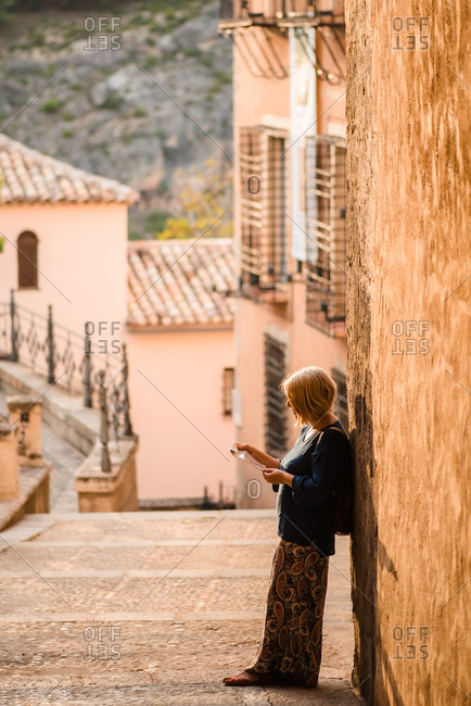 Positive side view of adult female tourist reading map and looking away with curiosity while standing against shabby stone wall of ancient building during sightseeing in old town Cuenca in Spain