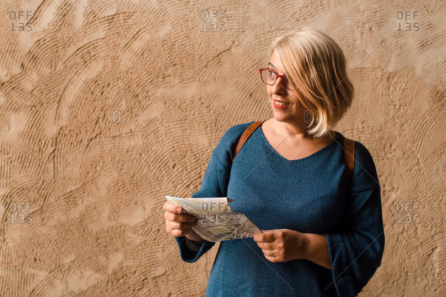 Positive adult female tourist reading map and looking away with curiosity while standing against shabby stone wall of ancient building during sightseeing in old town Cuenca in Spain