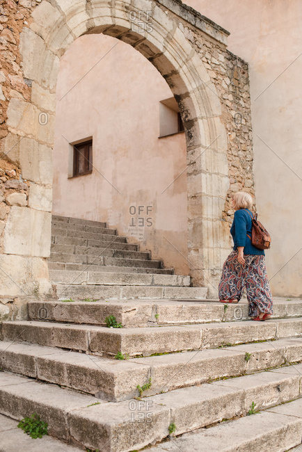 Side view of female tourist strolling up stone steps of medieval building with arched passage during sightseeing in Cuenca town in Spain