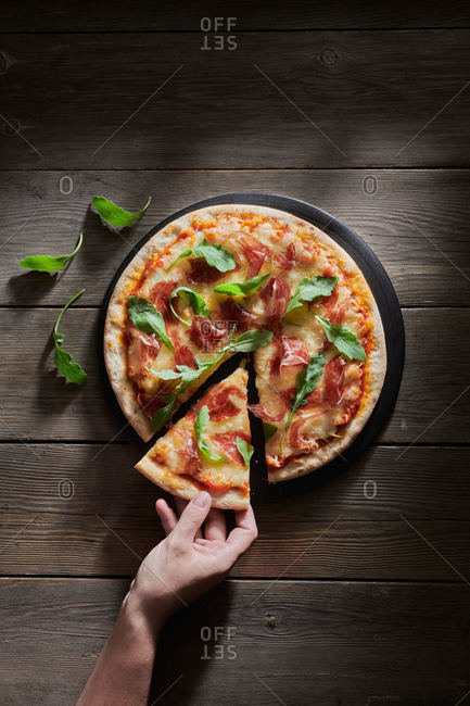 Top view of crop unrecognizable person with piece of delicious pizza decorated with fresh basil and arugula leaves