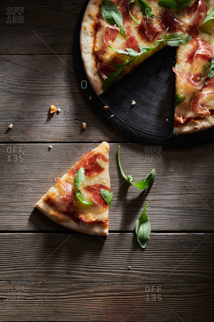 Top view of delicious pizza decorated with fresh basil and arugula leaves