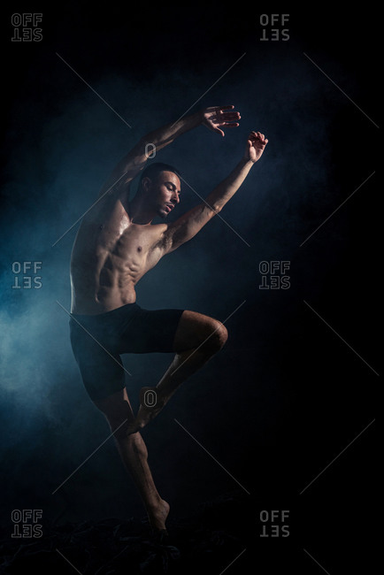 Full body of faceless tanned sporty shirtless dancer in shorts raising arm while doing dance move in dark room in light of lamp