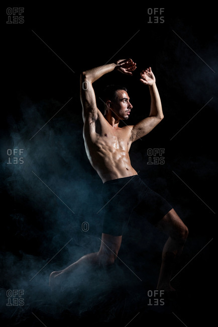 Full body of faceless tanned sporty shirtless dancer in shorts raising arm while doing dance move in dark room in light of lamp looking away