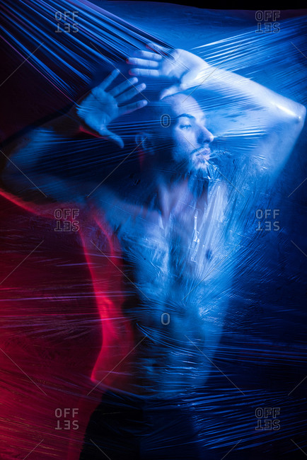 Pensive young handsome shirtless muscular male looking away while putting hands on surface of big transparent tape in light of blue and red lamps