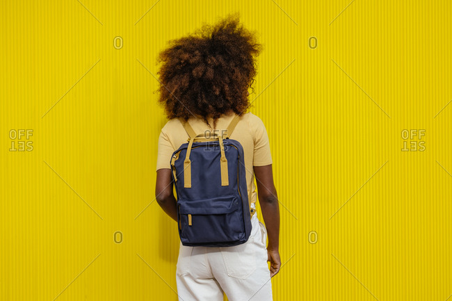 Back view black woman with afro hair with a backpack on her back