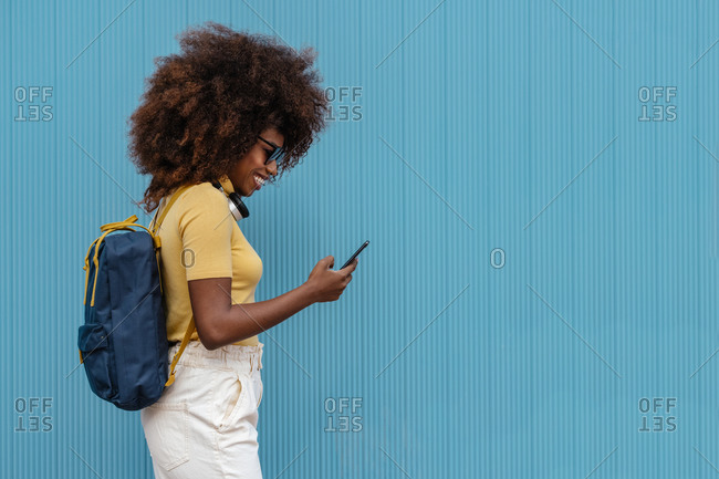 Black woman with afro hair listening to music on mobile in front of a blue wall