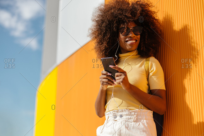 Black woman with afro hair listening to music on mobile in front of an orange wall
