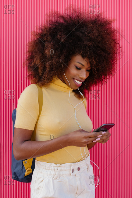 Black woman with afro hair listening to music on mobile in front of a pink wall