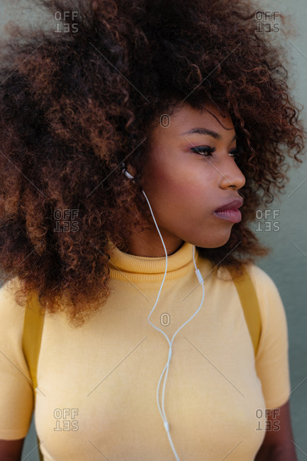 Black woman with afro hair listening to music with a backpack on her back