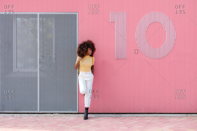 Black woman with afro hair posing in front of a pink wall looking away
