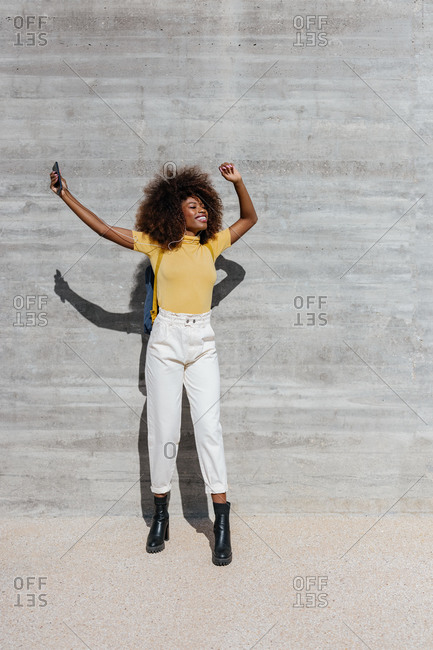 Black woman with afro hair listening to music on mobile in front of a gray wall