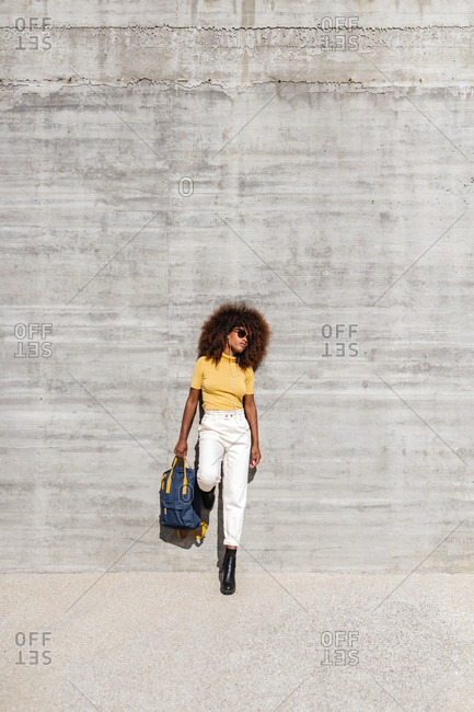 Black woman with afro hair listening to music on mobile in front of a gray wall holding a backpack with the hand