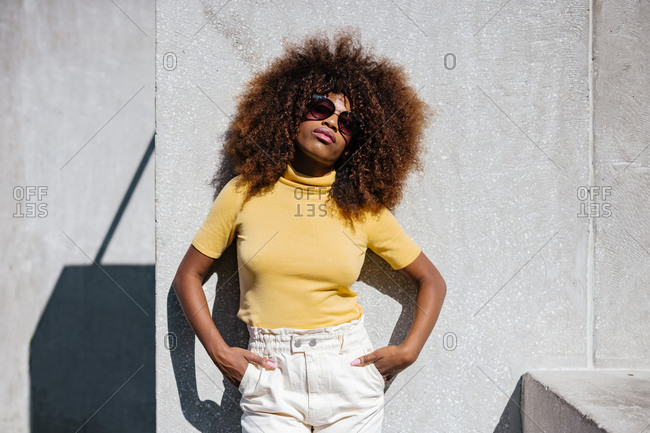 Black woman with afro hair posing in front of a gray wall looking at camera