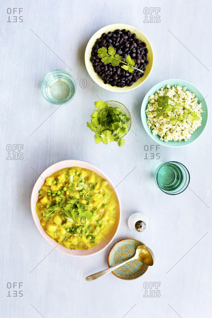 Potato pea curry with black beans and jade rice on light surface