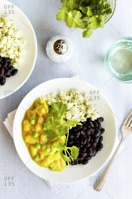 Potato pea curry with black beans and jade rice on a plate