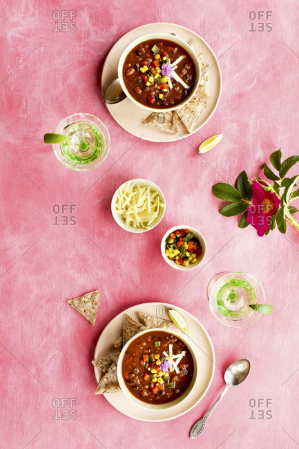 Spicy four bean chili on pink surface with cocktails
