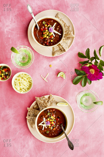Spicy four bean chili served in two bowls on pink surface with cocktails