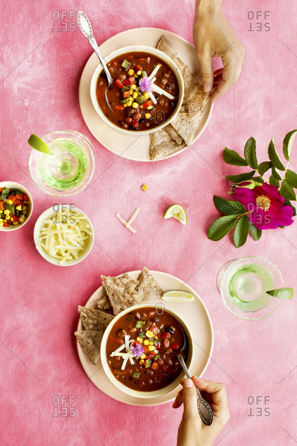 Two people eating bowls of spicy four bean chili on pink surface