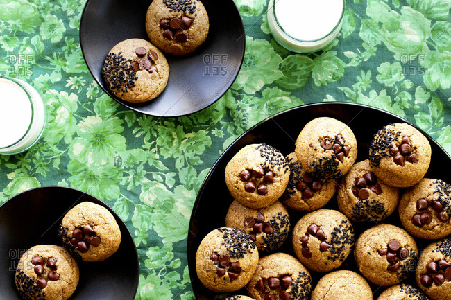 Toasted sesame chocolate chip cookies with milk on green surface