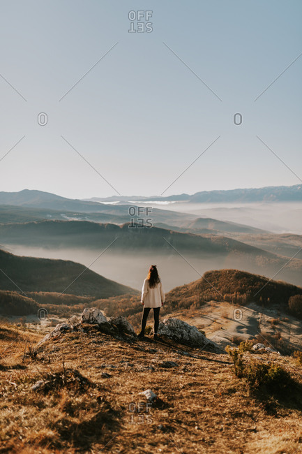 Rear view of woman overlooking foggy mountains in Bosnia and Herzegovina