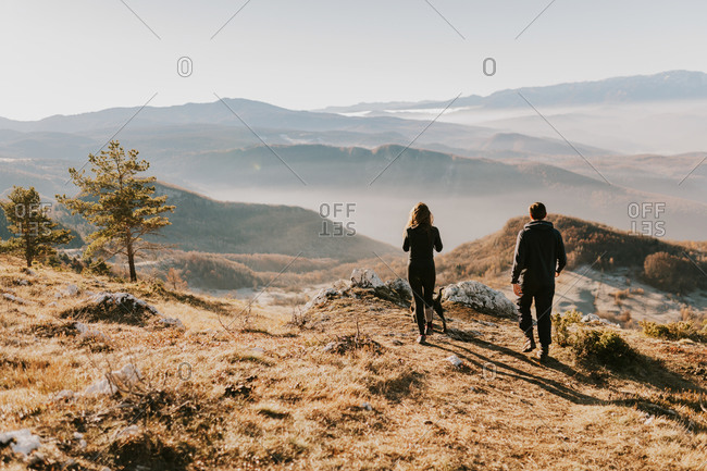 Rear view of couple overlooking foggy mountains in Bosnia and Herzegovina