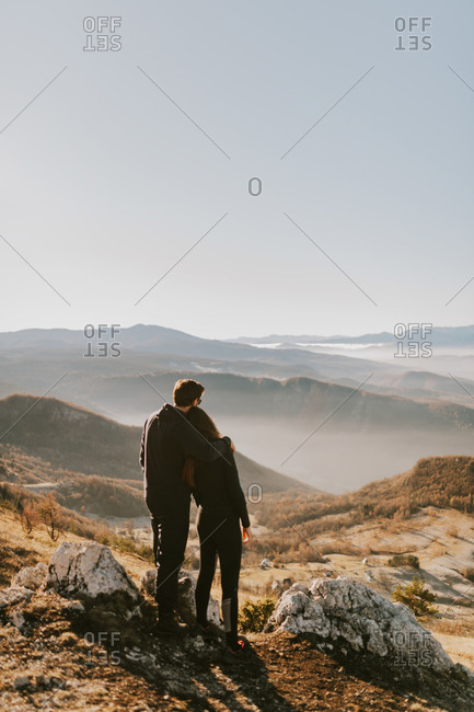 Couple embrace as they overlook a foggy mountain landscape in Bosnia and Herzegovina