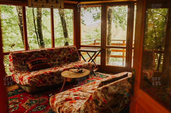 Interior of a cozy treehouse with red rug and furniture