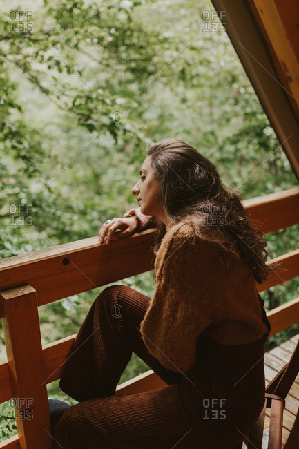 Woman sitting up in a wooden treehouse nestled in the forest