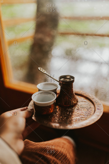 Woman drinking coffee in a treehouse while looking out window