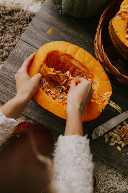 Overhead view of a woman removing seeds from a pumpkin