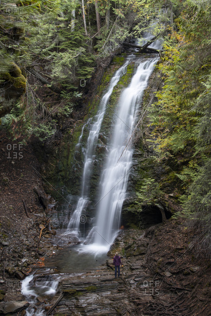 A hiker is dwarfed by a beautiful waterfall in Kaslo, British Columbia