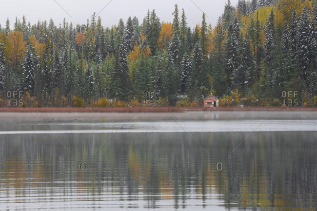 A cabin on a lake surrounded by fall color British Columbia