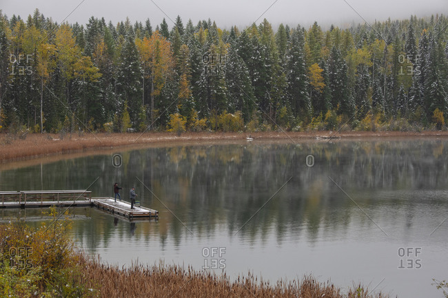 Fishermen on a calm lake surrounded by fall color In the interior of British Columbia