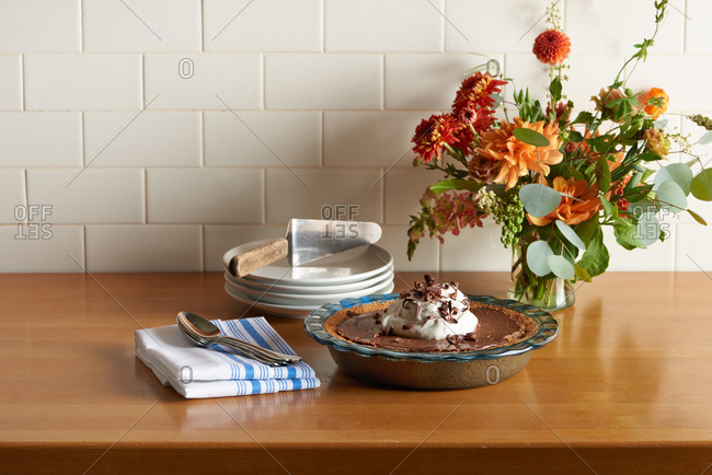Whole chocolate cream pie in a blue glass dish with a large dollop of fresh whipped cream and chocolate shavings on top