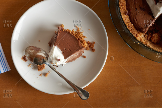 Sliced wedge of chocolate cream pie with spoon on a round white plate and wood surface