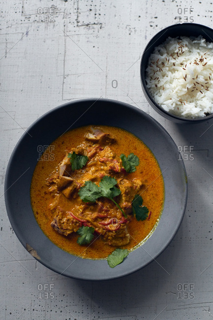 A homemade dish of butter chicken with rich curry spices topped with cilantro and served with a side of rice with cumin seeds
