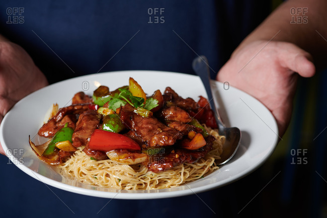 Chef's hands holding a plate of thin noodles with a lamb, ginger, scallion stir fry in a Chinese restaurant