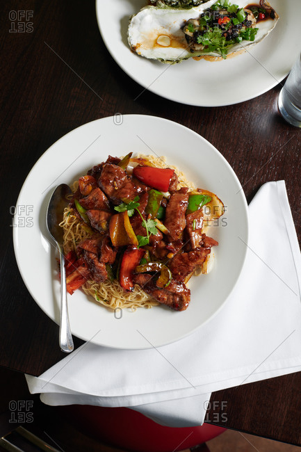A plate of thin noodles with a lamb, ginger, scallion stir fry in a Chinese restaurant by steamed oysters and black bean sauce