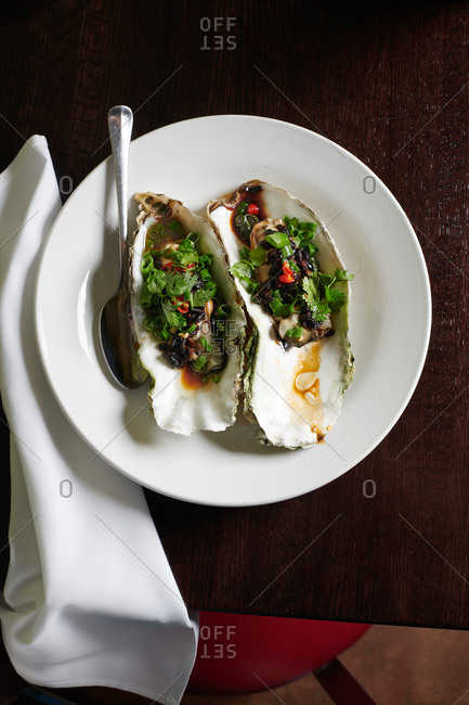 Two very large steamed oysters on a round white plate with black bean sauce served in a Chinese restaurant
