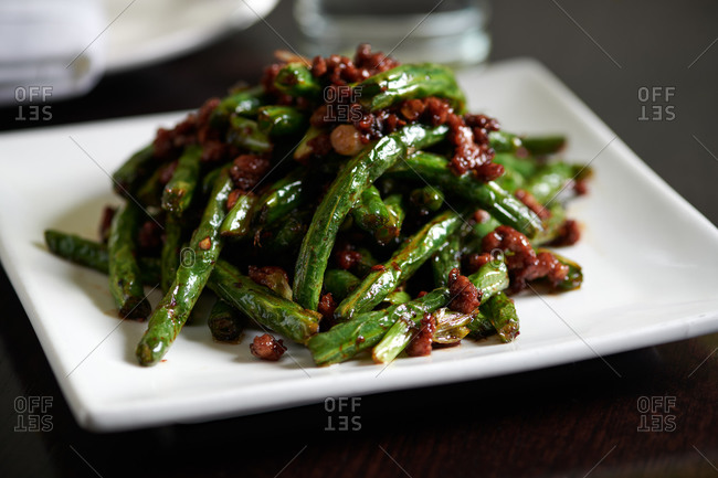 Green beans stir fried with ground pork and XO sauce in a Chinese restaurant served on a square white plate
