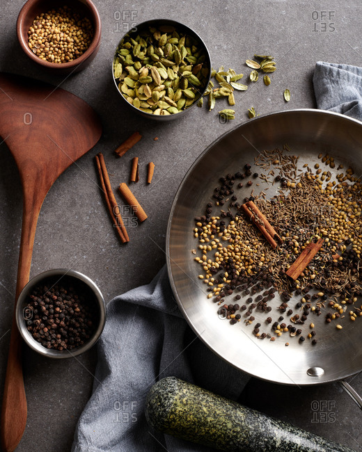 Spices for Garam Masala, arranged in a stainless steel pan for toasting with other spices nearby on a slate surface