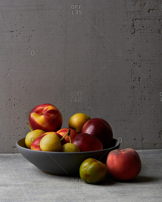 Fruit bowl still life with nectarines, peaches and Asian pears in a gray bowl with window light