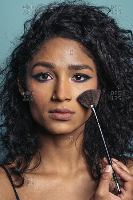 Beautiful young hispanic woman wearing colorful makeup looking at camera and holding a brush in Madrid, Spain