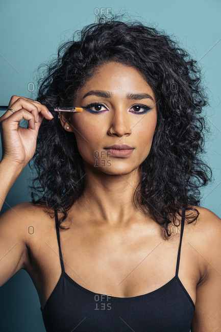Young hispanic woman wearing cool makeup using eye brush and looking at camera in Madrid, Spain